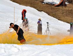 水しぶきをあげて水面を滑走する男性スノーボーダー=大町市平・鹿島槍黒沢高原