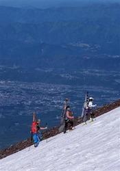 スキーを背負って7合目付近の斜面を登る登山者