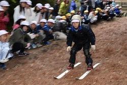 落ち葉の上を元気よく滑走する児童