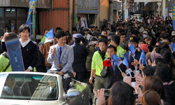 沿道からの歓声に車上から応える平岡選手(右)