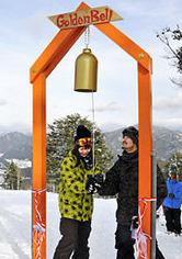 鐘を打ち鳴らしてモニュメントの完成を祝う若者たち=高山市久々野町無数河、ひだ舟山スノーリゾートアルコピア