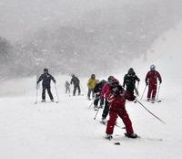 吹雪のなか、スキーを楽しむ観光客(猪苗代町の箕輪スキー場で)