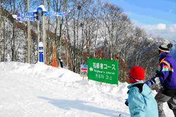 「初級者コース」と表示のある林間コースに入る家族連れ。雪崩の危険がある場合、閉鎖される=7日、小谷村の栂池高原スキー場