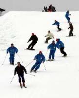 人工雪を敷き詰めたゲレンデを滑り降りるスキーインストラクターら(午前10時50分、高島市今津町・箱館山スキー場)