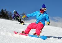 心地よい風を受けながら、スノーボードで滑走を楽しむ人たち