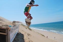 鳥取砂丘で開催された国内唯一のサンドボード大会で披露された「ストレートジャンプ」。スノーボードよりも一回り小さい専用の板にはだしで乗り、約30度の砂斜面を日本海に向かって一気に滑り降りる=8月28日