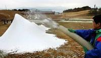 ホースから勢いよく吹き出し、山のように積もる人工雪(高島市今津町・箱館山スキー場)