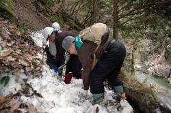 三段峡の遊歩道に残った雪をスコップで取り除く組合員たち