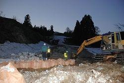 崩落斜面から流れてきた泥と水の流路を確保するため土のうを置く作業員ら=27日午後6時半すぎ