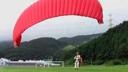 パラグライダーの体験会に先駆けて行われた試験飛行=7月、佐賀市富士町の天山スキー場(佐賀市観光協会提供)