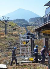 御岳山を背にリフトの取り付け作業に励む社員ら=高山市高根町日和田、チャオ御岳スノーリゾート
