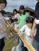 竹水路を流れてくるそばを上手にすくい取る参加者=米沢市・小野川スキー場