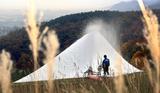 ススキの穂が揺れ、紅葉が色付く中で進む降雪作業=小樽市春香町のスキー場「スノークルーズオーンズ」で、尾籠章裕撮影