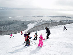 陸奥湾を見下ろすゲレンデで滑りを楽しむ子どもたち=9日午前、むつ市の釜臥山スキー場