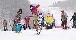 人工雪コースで初滑りを楽しむスノーボーダーら=18日、香美町村岡区大笹のハチ北スキー場