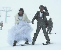 手をつないで滑走する新郎新婦=栂池高原スキー場で光田宗義撮影