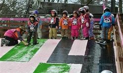 雪のない人工芝の坂道で滑り降りる練習をする子供たち=11日、長野県軽井沢町の軽井沢プリンスホテルスキー場(村島有紀撮影)