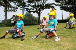 天然芝の斜面を気持ちよさそうに滑る子どもたち=香川県高松市香南町、さぬき空港公園