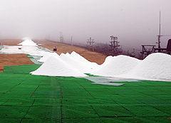 造雪機によってつくられた雪の山が並ぶ=27日午後