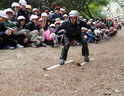 声援を受けながら落ち葉スキーに挑戦する児童=愛知県岡崎市で2010年11月12日、竹内幹撮影