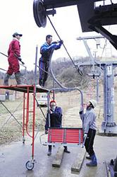 スキーシーズンを前に、リフトの座席を取り付ける職員ら=七尾市多根町で