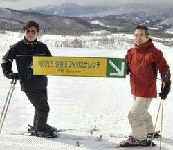 案内板を持ち笑顔の若杉社長(右)とチョン社長(読売新聞社)