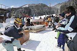 滑走前にユニークな手作りそりの説明をする「そりコンin大町」の出場者(左)=23日、大町市の鹿島槍スキー場