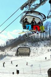 青空が広がる中、雪の感触を楽しむスノーボーダーら