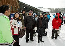 大佐スキー場のスタッフ(左端)から説明を聞く韓国からのモニターツアーの一行