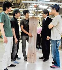 スノーボードの試作品を囲む日野さん(右から2番目)と玉田さん(右から3番目)ら=高山市の飛騨産業で