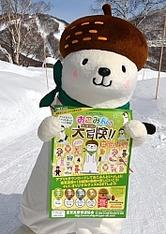 新企画のポスターを持つ志賀高原のPRキャラクター「おこみん」