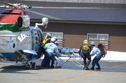 救助された人をヘリから降ろす訓練をする消防隊員ら=24日、湯沢町