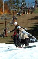 シーズンに先駆けてオープンしたスキー場でスノーボードを楽しむ若者たち