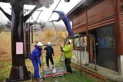 雨の中、リフトを取り付ける職員=恩原高原スキー場