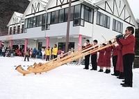 雪上でアルプホルンを演奏する愛好者