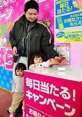 携帯電話を使ってキャンペーンに応募する親子連れ