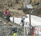 スキーの板やスノボードを担ぎ、通行禁止区域の登山道を降りてくる愛好者