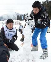 倒れないように雪玉を積み上げる出場者=2日、香美町村岡区大笹のハチ北スキー場