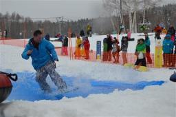 スノーボードで水を切って池を渡る参加者