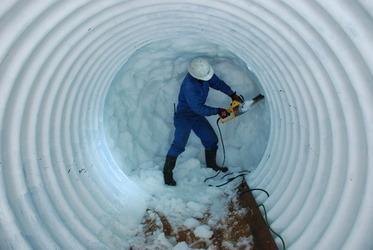 硬い雪をチェーンソーで切りながら、かまくらを作る