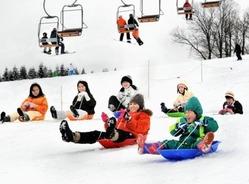 新雪のゲレンデでそり遊びを楽しむ家族連れら14日、福井県勝山市のスキージャム勝山