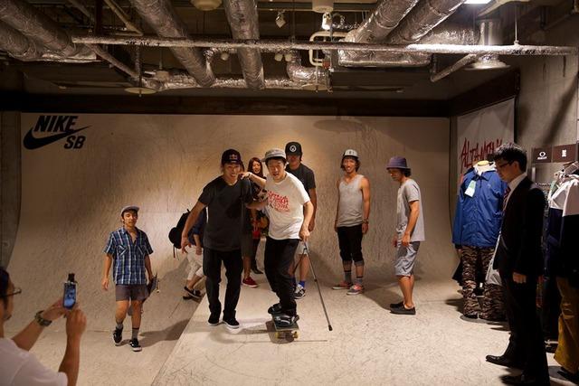 角野に支えられながらスケートボードに乗る岡本