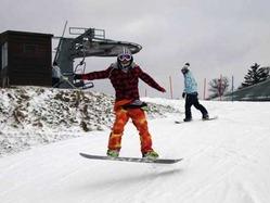 オープンしたばかりのゲレンデでスノーボードを楽しむ若者たち