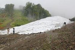 五輪本番での雪不足に備えて保存されている雪の山。断熱シートで覆われている=ロシア・ソチで2013年8月7日、田中洋之撮影