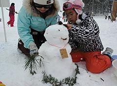雪だるまの飾り付けに没頭する参加者