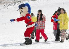 SKE48のメンバーに応援されながら、へっぴり腰で滑るドアラ(左)=岐阜県高山市のチャオ御岳スキーリゾートで