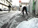 市街地では今冬初めての積雪となり、雪かきをする住民