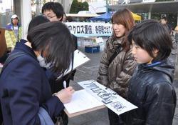 屋内スノーボード場「アクロス重信」の存続を求め署名活動をする人たち=22日、松山市