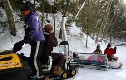 ガイドの話を聞きながら、森の中の「雪上ドライブクルージング」を楽しむ家族連れ=高山市一之宮町の位山