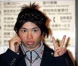 帰国した成田童夢は、電話をかけながら写真を求めるファンに向かってVサイン
